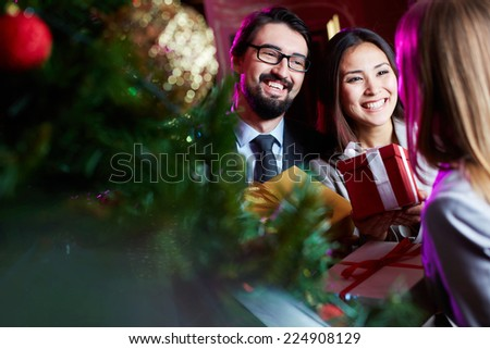 Happy employees congratulating their colleague on Christmas - stock photo
