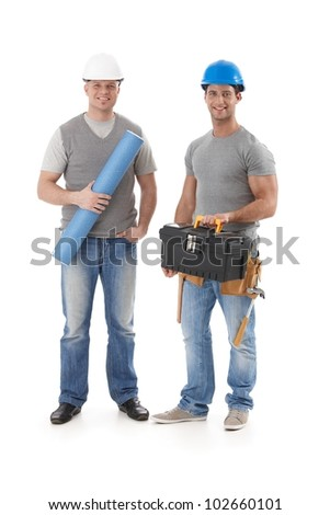 Happy engineer and builder workman standing with tools and floor plan, smiling at camera, isolated on white. - stock photo
