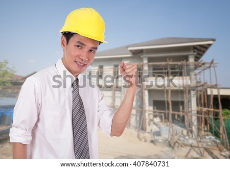 Happy engineer celebrating with arm raised, concept of successful, house construction background - stock photo