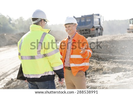 Happy engineer talking to colleague at construction site on sunny day - stock photo