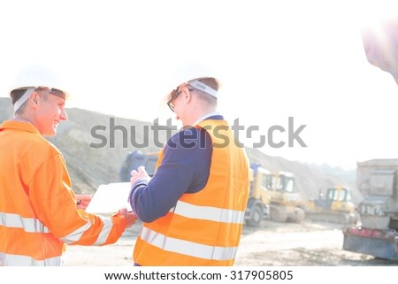 Happy engineers discussing over clipboard at construction site against clear sky - stock photo