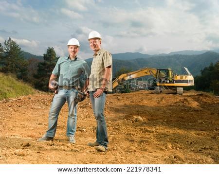 happy engineers on construction site - stock photo