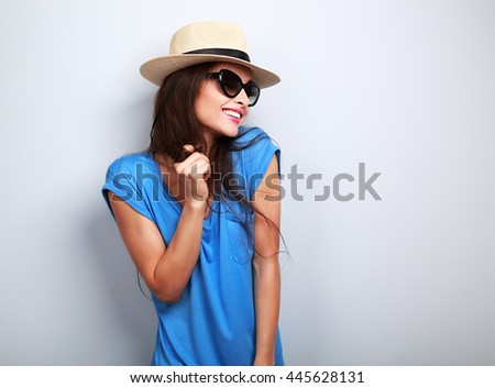 Happy enjoyment young woman in sun glasses and hat posing on blue background - stock photo
