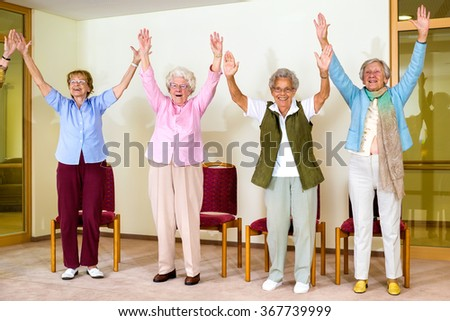 Happy enthusiastic group of senior women doing a physical workout in a seniors gym standing laughing and smiling with their hands raised into the air - stock photo