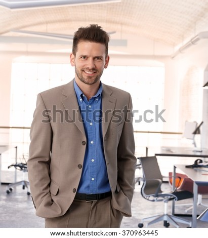 Happy entrepreneur at contemporary office, wearing suit, smiling. - stock photo
