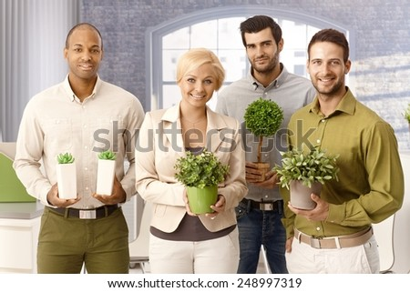 Happy environment friendly businessteam smiling, holding green plants, looking at camera. - stock photo