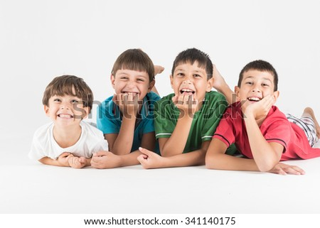 Happy epxressions from four children in group laying - stock photo