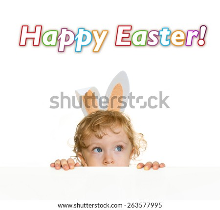 Happy ester greetings. Cute child with Easter rabbit ears on the table edge.  - stock photo