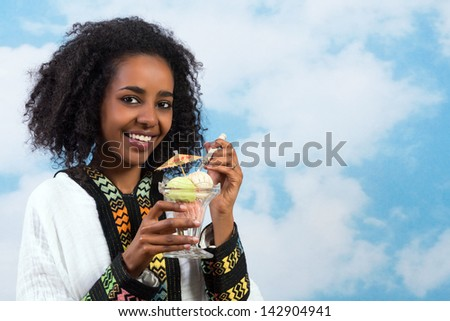 Happy Ethiopian girl wearing a traditional costume eating icecream - stock photo