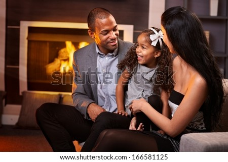 Happy ethnic family of three in living room by fireplace. - stock photo