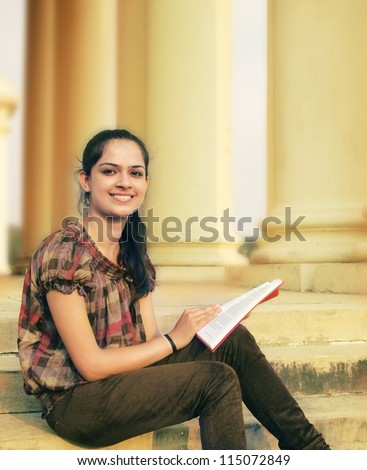Happy ethnic Indian / Asian college student studying on campus - stock photo
