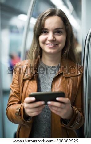 happy european brunette girl using cell phone and smiling at subway