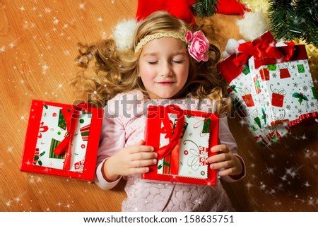 Happy european girl with long blond curly hair and flower on it lies under Christmas tree with her presents and closed eyes, making her wish - stock photo