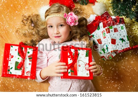 Happy european girl with long blond curly hair and flower on it lies under Christmas tree with her preents  - stock photo