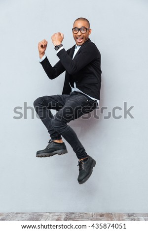 Happy excited african american young man jumping and celebrating success - stock photo
