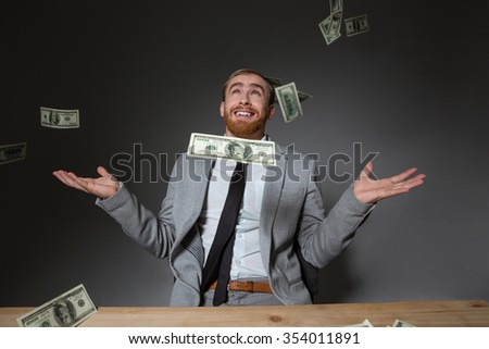 Happy excited business man in grey suit enjoying with rain of money over grey background - stock photo