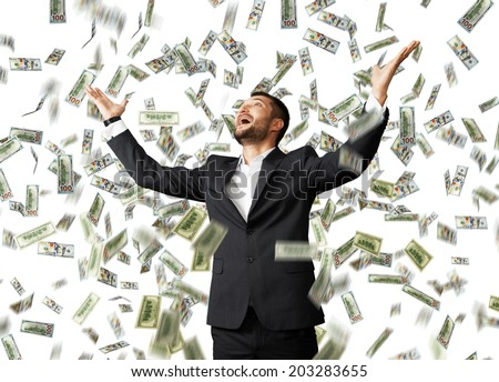 happy excited businessman raising hands up and looking up under money rain - stock photo