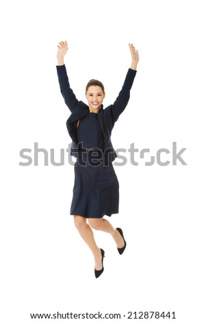Happy excited businesswoman jumping with hands up - stock photo