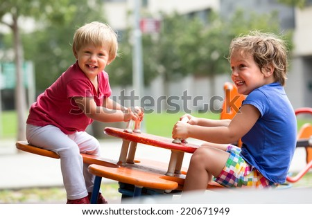 Happy excited children having fun at playground in sunny day  - stock photo