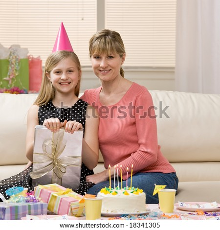 Happy, excited girl and mother sit with birthday gifts and birthday cake