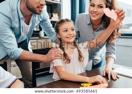 happy excited girl showing carved heart to parents