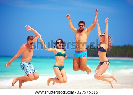 happy excited group of young friends jumping on summer beach - stock photo