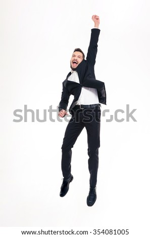 Happy excited handsome young businessman with beard in classic suit and shoes jumping and celebrating success over white background - stock photo