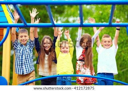 happy excited kids having fun together on playground - stock photo