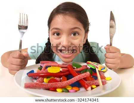 happy excited Latin female child holding fork and knife sitting at table ready for eat a dish full of candy , lollipop and sugary things in unhealthy sweet nutrition and kid in sugar abuse concept - stock photo