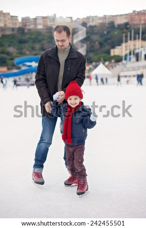 Happy excited little boy and his young father learning ice-skating outdoor - stock photo