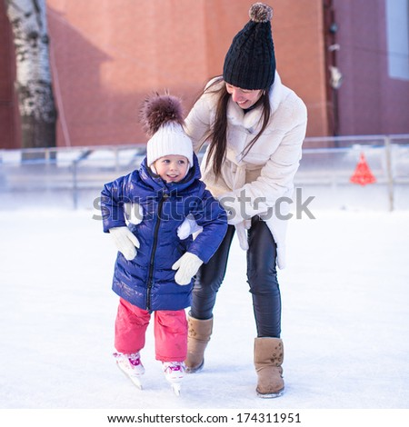 Happy excited little girl and her young mother learning ice-skating - stock photo