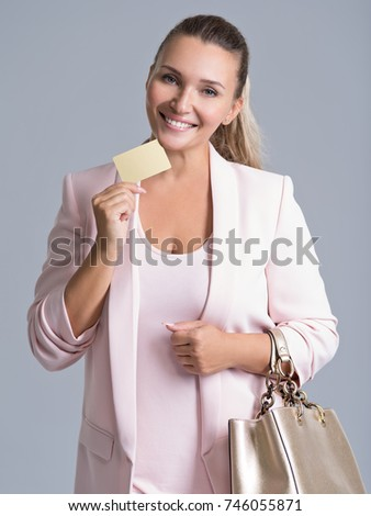 Happy excited surprised young woman with credit card over white background