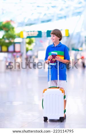 Happy excited teenager boy traveling alone by airplane, standing at Dusseldorf airport terminal with suitcase holding his passport and boarding pass getting ready to fly for school exchange trip - stock photo