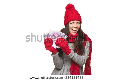 Happy excited winter woman holding euro cash money, over white background, with copy space - stock photo