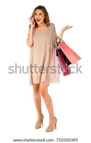 Happy excited woman in dress carry colored paper shopping bags, talking on the cell phone, holding smartphone. Isolated on white background