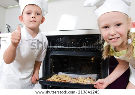Happy excited young children dressed in white chefs uniforms grinning at the camera as they place a baking tray with homemade pizza in the oven that they have just made themselves - stock photo