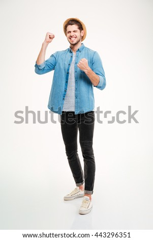 Happy excited young man standing and celebrating success over white background - stock photo