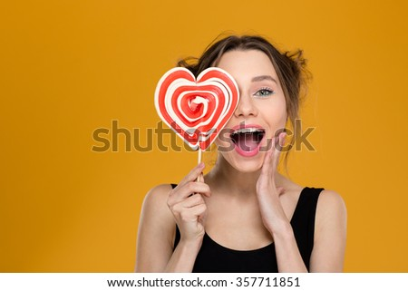 Happy excited young woman covered her eye with bright heart shaped lollipop over yellow background - stock photo