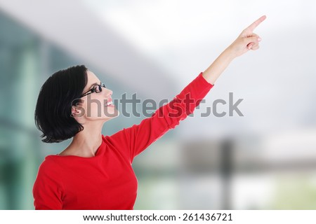 Happy , excited young woman pointing on copy space - stock photo
