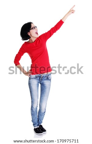 Happy , excited young woman pointing on copy space, isolated on white