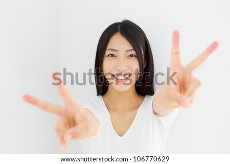 happy excited young woman showing the sign of victory - stock photo