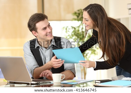 Happy executive or secretary giving documents to a businessman in a desktop at office - stock photo