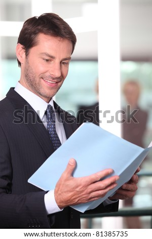 Happy executive reading a report - stock photo