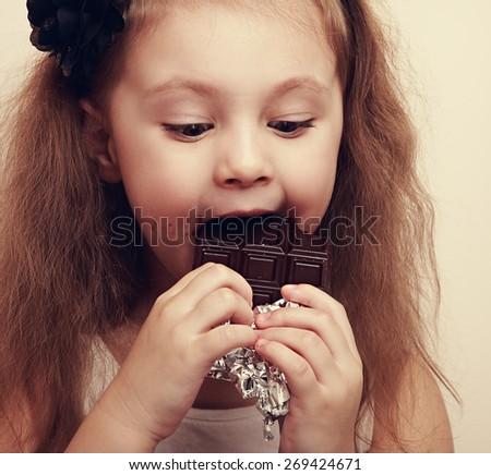 Happy expression kid girl biting dark chocolate. Closeup vintage portrait - stock photo