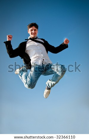 Happy expressive man jumping high on blue sky - stock photo