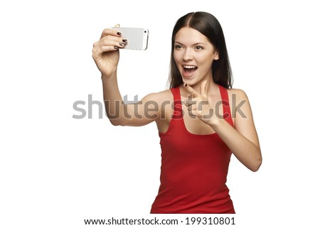 Happy expressive young woman pointing at camera while taking pictures of herself through cellphone, over white background - stock photo