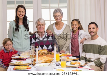 Happy extended family at christmas dinner posing at camera at home in the living room - stock photo