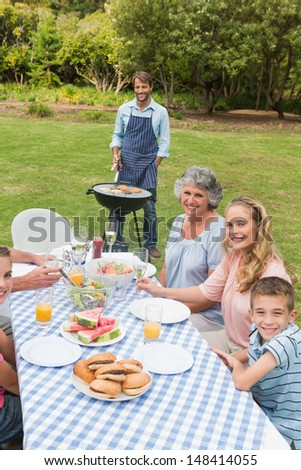 Happy extended family having a barbecue smiling at camera outside - stock photo
