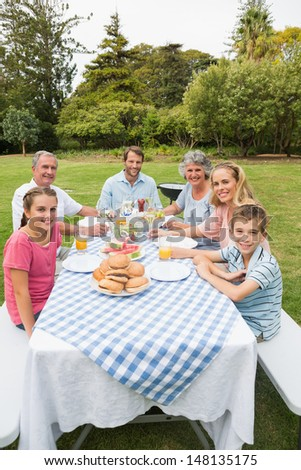 Happy extended family having dinner outdoors at picnic table smiling at camera - stock photo