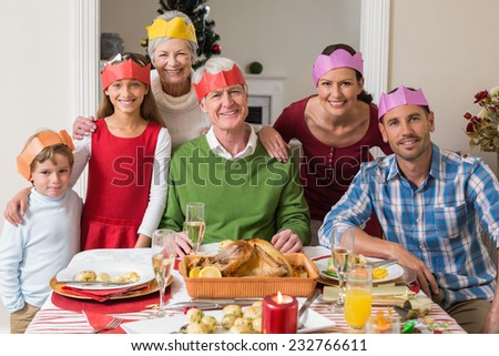 Happy extended family in party hat at dinner table at home in the living room - stock photo